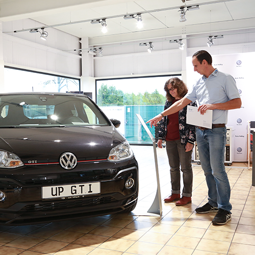 Verkäufer berät Kunden zu VW GTI